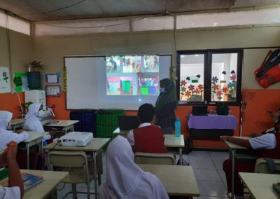 Erlena stands in front of a classroom of children, projector on with images of their upcycled trashcans made of plastic bottles, the room is full of fifth grade students