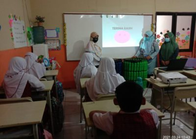 Erlena and Dr. Ishak thank the students for listening, with a projector in the front of the class and students sitting at desks facing the projector screen