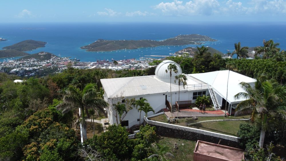 A small observatory building, with a dome housing a telescope, overlooking the Caribbean city of Charlotte Amalie and the deep blue Caribbean Sea